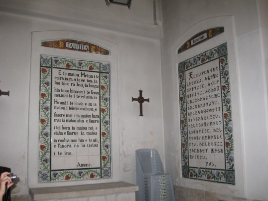 Photo of two plaques on a wall. On the left is a text of the Lord's Prayer in Tahitian; on the right is the text in Japanese. A cross hangs on the wall between them.